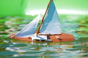 Traditional small wooden sailing boat in the pond of park